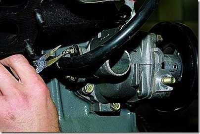 Круглогубцами ослабляем хомут крепления к патрубку отводящей трубки радиатора отопителя шланга отвода охлаждающей жидкости от дроссельного узла (двигатель ВАЗ-21214) или от блока подогрева карбюратора (ВАЗ-21213).