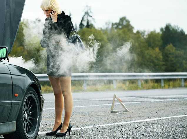 Девушка стоит на дороге около сломавшегося автомобиля